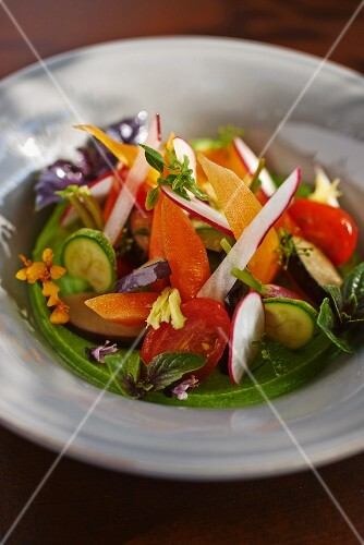 Spring vegetable soup with edible flowers