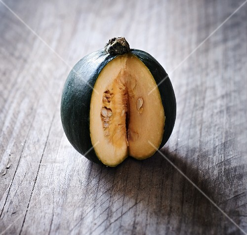 A green squash, sliced to show the centre, on a wooden surface