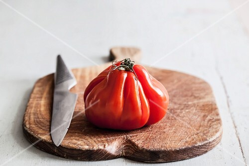 A beef tomato with a knife on a chopping board