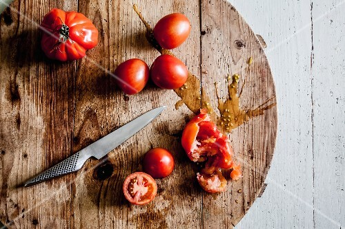 Several tomatoes, some sliced or crushed, on a round wooden board