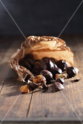 Chestnuts in a paper bag on a wooden table