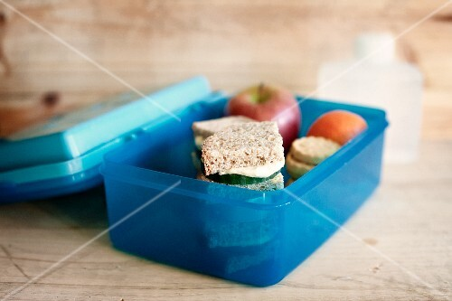 An open lunch box with a cucumber sandwich, fruit and biscuits