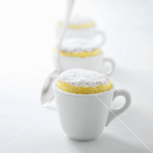 Three lemon soufflés with icing sugar in cups