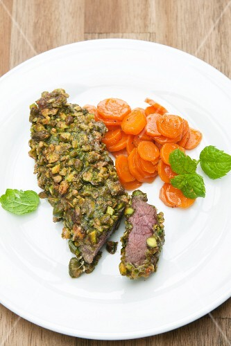 Leg of venison steaks baked in pistachio crust with honey carrots