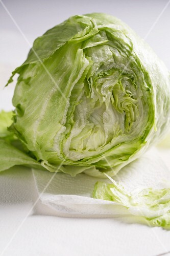 A partly sliced fresh iceberg lettuce