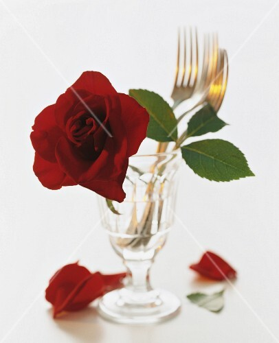 Forks and a rose in a decorative glass
