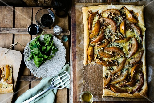 Puff pastry tart with pears, blue cheese, walnuts and rocket, one slice served