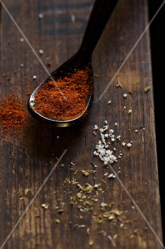A spoonful of chilli powder and assorted spices on a wooden board