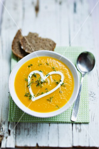 Carrot soup garnished with a heart of sour cream and cress