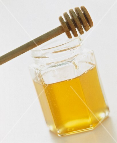 A jar of honey with a honey dipper