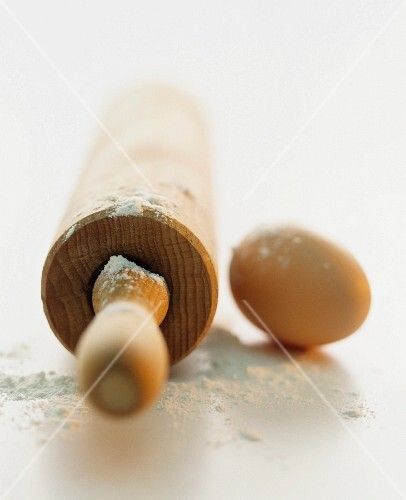 A still life featuring a rolling pin, flour and an egg