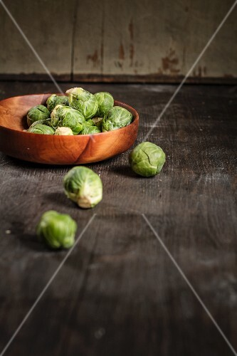 Brussel sprouts in a wooden bowl on a wooden table