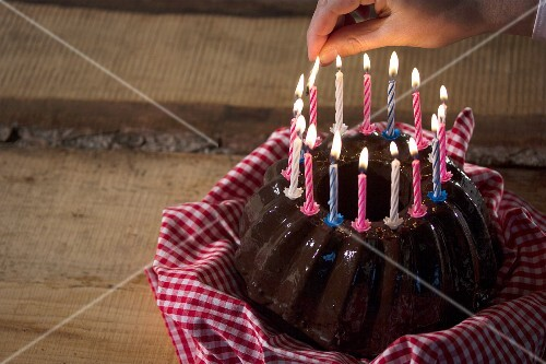 Candles being lit on top of a chocolate Bundt cake