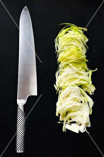 Sliced white cabbage with a Japanese kitchen knife on a black background