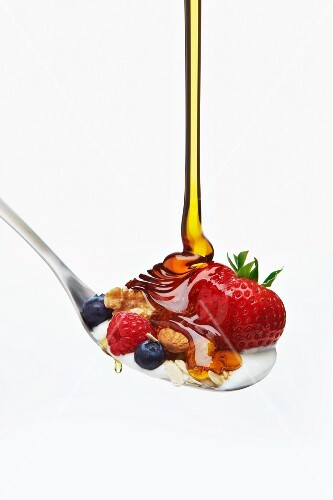 Honey Flowing on a Spoon with Berry Muesli