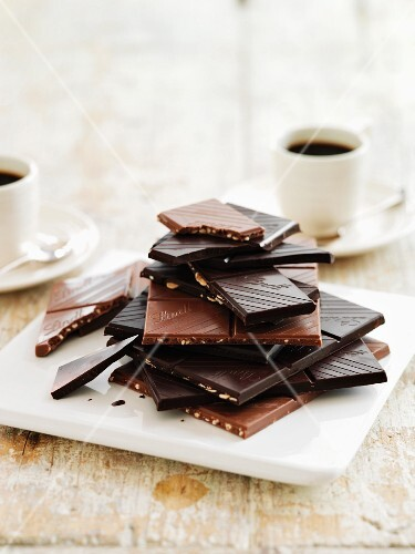 Pieces of chocolate, stacked and coffee cups