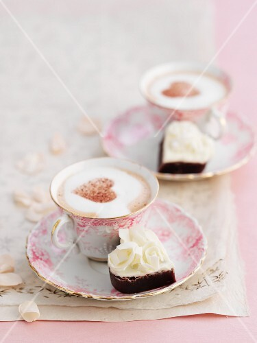 Petit fours and cappuccino decorated with cocoa powder hearts