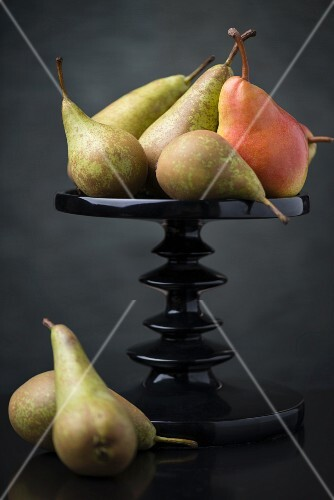 Several pears on and next to a cake stand