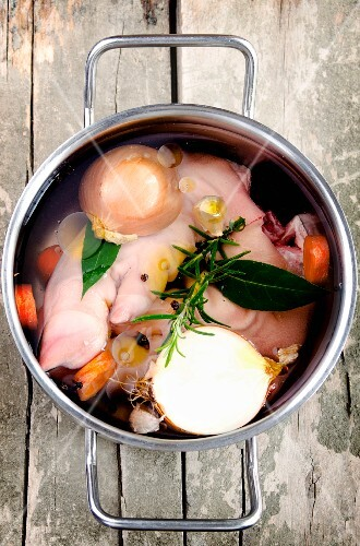 Pig's trotters in a pot with onions, bay leaves, carrots, rosemary, garlic and peppercorns