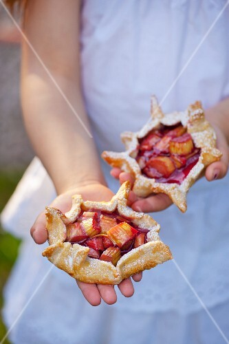 Little girl holding rhubarb tartlets