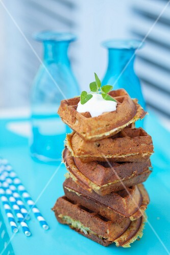 Triangular courgette waffles with yoghurt and mint leaves
