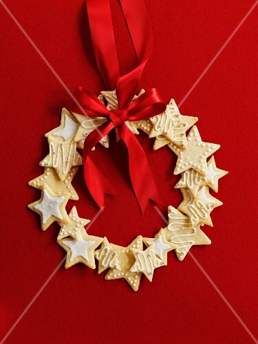 Wreath made of star cookies with a red ribbon in front of a red background