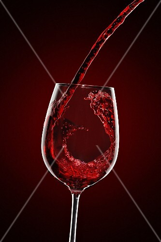 Red wine being pouring into a wine glass