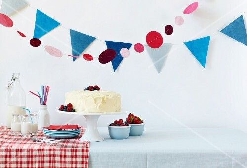 Birthday Table with a White Frosted Cake and Fresh Berries; Milk