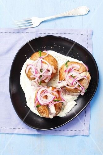 Baked potatoes with herring and red onions