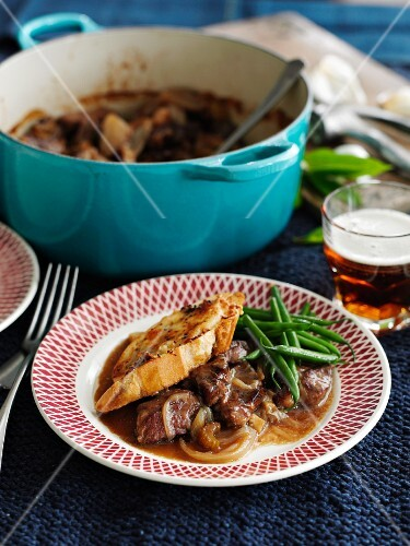 Beef and beer stew with cheese croutons, onions and green beans