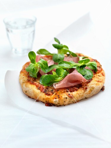 Mini pizza with lamb's lettuce and dry-cured ham