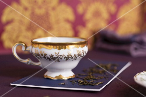 A teacup with a gold edge and leaves of green tea