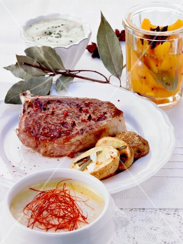 A meal of chilli soup, a veal chop and preserved peaches