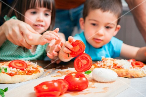 Children helping to top pizzas