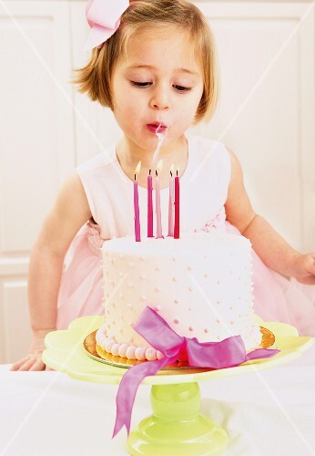 Girl blowing out candles on a birthday cake