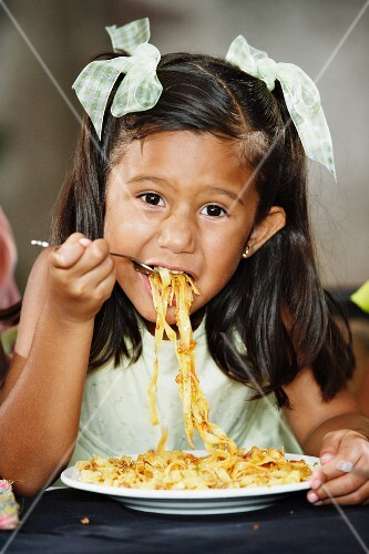 Small girl eating pasta