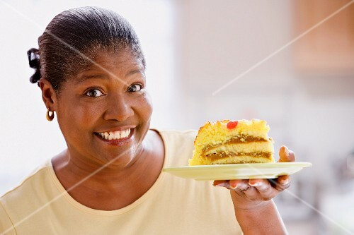 Middle-aged African woman smiling and holding up a piece of cake
