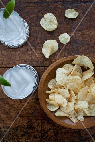 Two glasses of gin and tonic with ice cubes, and a wooden bowl of crisps