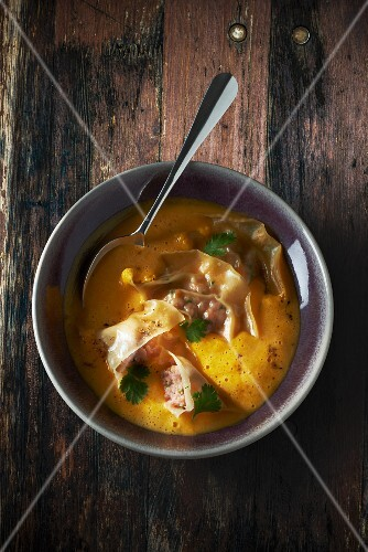 Butternut squash soup with ravioli and prawns