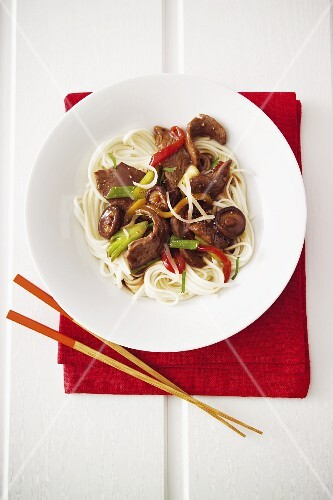 Japanese dish of beef with mushrooms and spring onions on a bed of noodles