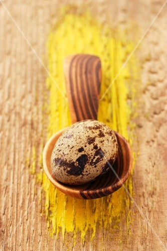 A quail's egg on a wooden spoon