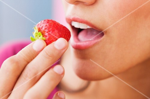 Close up of Hispanic woman eating strawberry