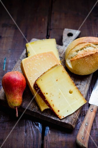 Various types of cheese from Germany with a pear and a bread roll