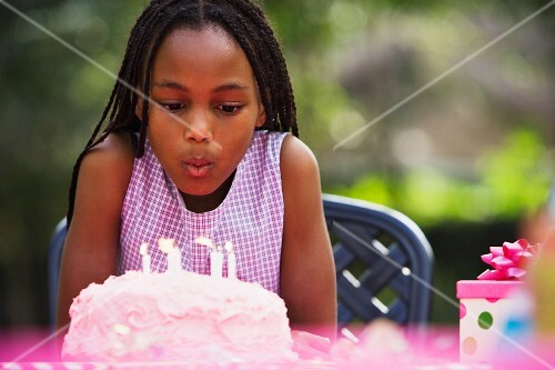 African girl blowing out birthday candles