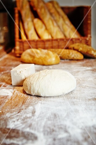 Unbaked bread and yeast, baked white loaves and baguettes