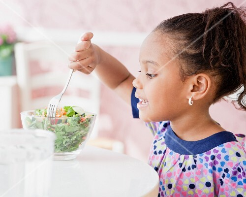 African girl eating salad