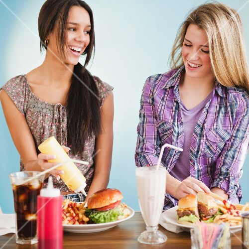 Teenage girls eating hamburgers and french fries