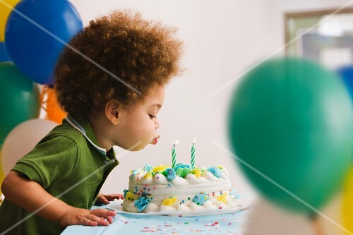 A boy blowing out birthday cake candles