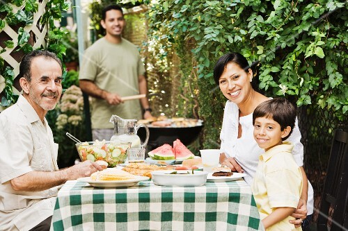 Multi-generational Hispanic family eating on patio