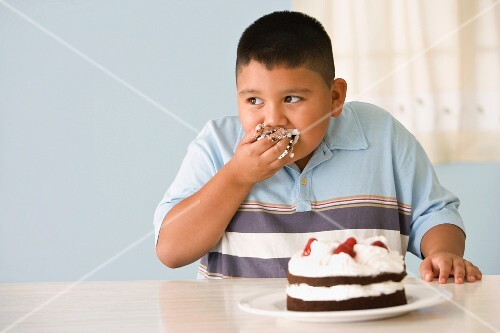 Hispanic boy eating cake with hand